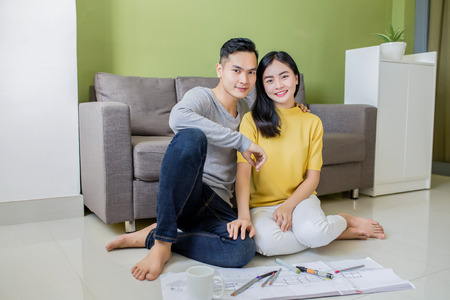 Happy asian couple planning their new apartment 免版税图像