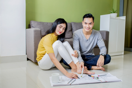 Happy asian couple planning their new apartment Reklamní fotografie