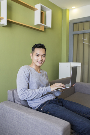 Asian man at home on sofa using a laptop. 免版税图像