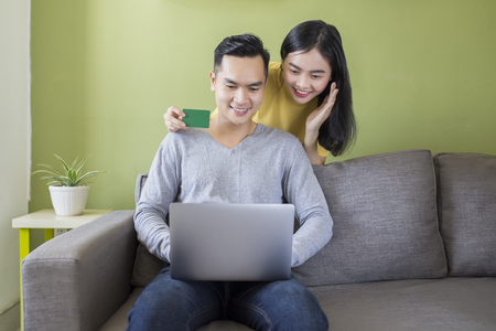 Happy asian couple working together with the laptop