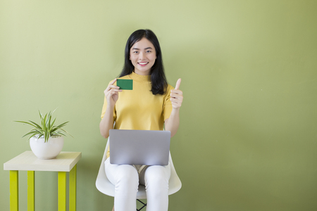 Asian woman at home on chair using a laptop with credit card