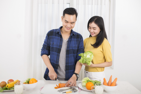 Loving asian couple cooking together in the kitchen at home 免版税图像