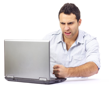 Portrait of an angry businessman at his laptop, on white background