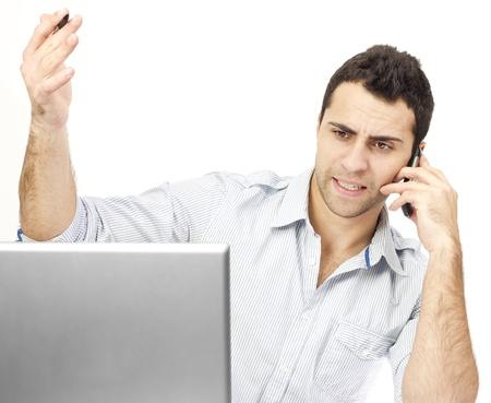 彼のラップトップの前に電話の怒っているビジネス男。彼の顔に狂牛病の式です。白い背景。