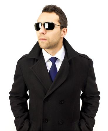 サングラスで、深刻な立っている男の肖像画のポケット、青いネクタイ、白いシャツと白の背景に手します。 写真素材