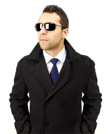 undercover agent: Portrait of a serious standing man with sunglasses, hands in pockets, blue tie, white shirt and white background. Stock Photo