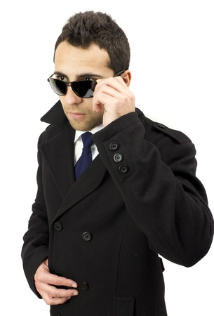 Portrait of a serious standing man with sunglasses, hands on his glasses, blue tie, white shirt and white background. photo