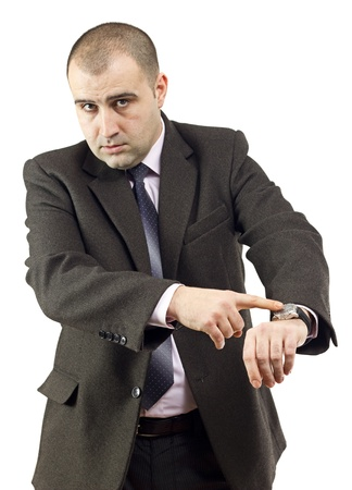 Serious adult businessman pointing to his watch.White background.