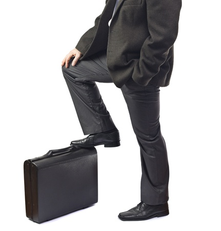 Business man waiting with foot on briefcase.White background. photo