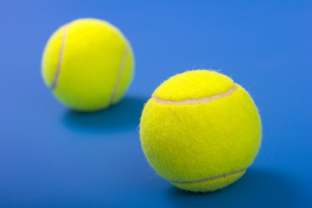 fairplay: Two tennis balls on a blue background.Focus in the foreground.