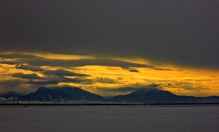 Beautiful and cloudy winter landscape at dawn.Orange sunset between clouds.Field and mountains covered with snow. photo