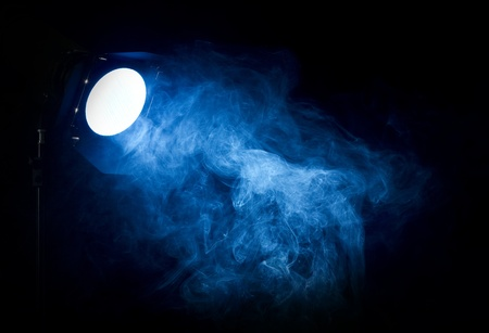 emptiness: Vintage theater blue light beam from projector on black background, illuminating smoke.Barn doors and grid used for light directing. Stock Photo