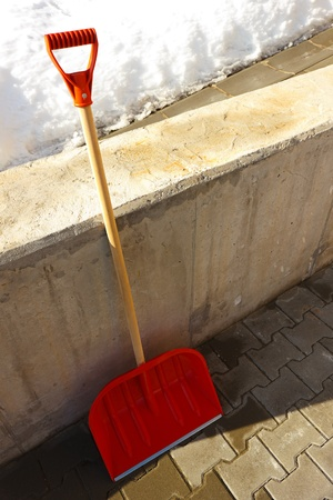 Red wooden shovel leaning against the wall.Snow in background.Winter season. Stock Photo - 12964469