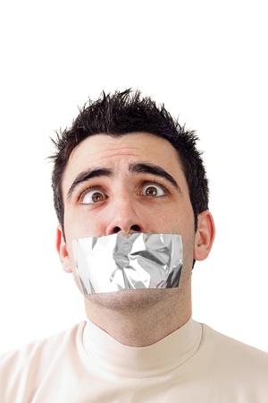 若い男が彼の口に灰色のダクトテープを持っています。彼の表情に役立ちます。白の背景