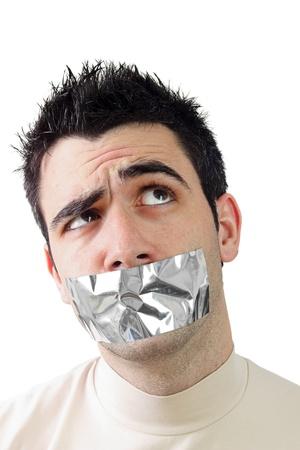 若い男が彼の口に灰色のダクトテープを持っています。彼の表情を疑問に思います。白の背景 写真素材