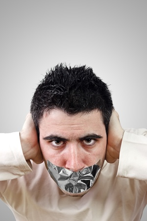 Angry young man having gray duct tape on his mouth.Gradient background with copy space. photo