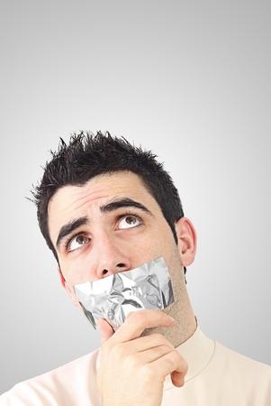 好奇心が強い若い男が彼の口に灰色のダクトテープを持っています。コピー スペースでのグラデーションの背景。