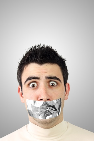 Scared young man having gray duct tape on his mouth.Gradient background with copy space. photo