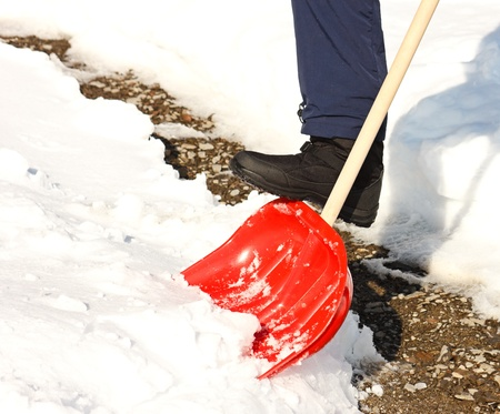 雪かき赤シャベルで男のクローズ アップ。バック グラウンドでの洗浄のパス。