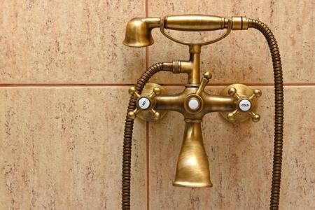 ビンテージの浴槽の蛇口とバック グラウンドでのセラミック タイル。レトロな青銅の外観。