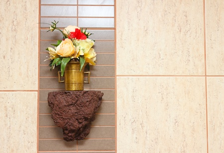 Ornamental color flowers in the bathroom, hanging on wall against tiles background. photo