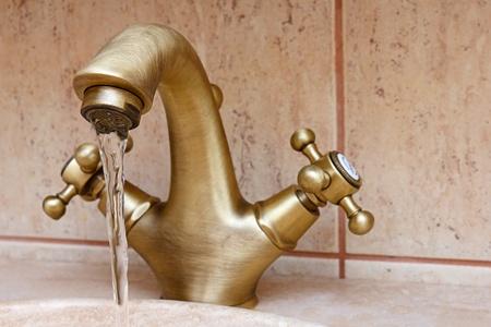 ヴィンテージやレトロなバスルーム蛇口から流れる水。セラミック タイルの背景と視点のビューで。 写真素材