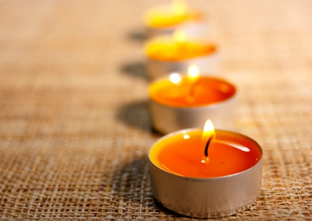 Four aligned burning orange candles placed on jute material.Possible decoration for Christmas or Easter. Religious objects. photo