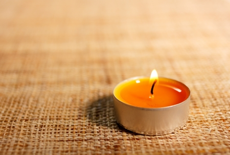 Burning orange candle placed on jute material.Possible decoration for Christmas or Easter. Religious object. photo