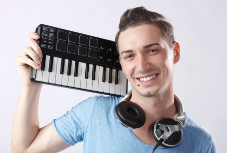Portrait of young smiling deejay with headphones and midi keyboard on his shoulder Piercing near mouth  photo