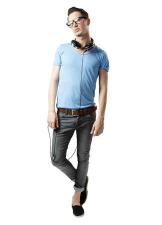 Attractive guy posing while having headphones on neck.Brown belt and grey pants. photo