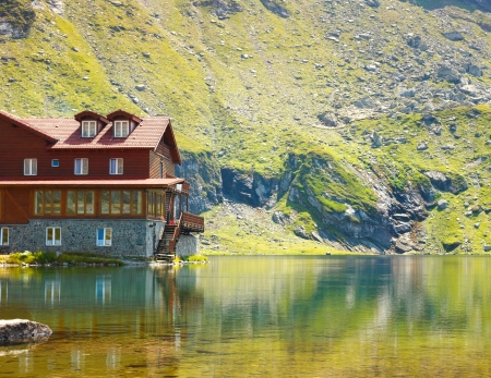 Red wooden house on glacier lake with very clean water.