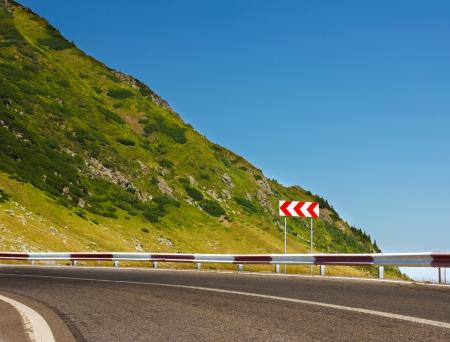 安全標識危険なカーブの前に山の道で。青い空にテキスト用のスペースをコピーします。