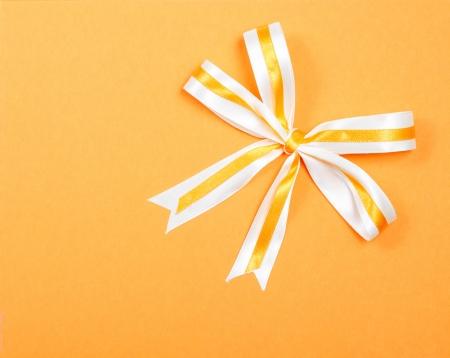 Top view of simple elegant ribbon on orange carton background  photo