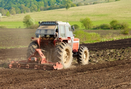 traction: Red tractor working the ground in spring  Stock Photo