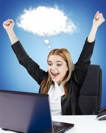 Successful business woman sitting at her desk in front of laptop. White cloud for custom text. photo