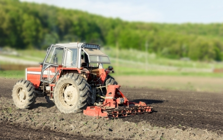 traction: Red tractor working the ground in spring season. Blurred background.