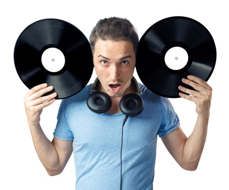 Shocked young man posing to camera while holding two black vinyl disks near his head. Isolated on white background. photo