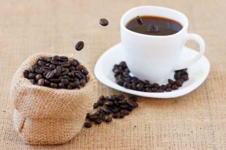 Coffee beans jumping from brown jute bag into white cup. photo