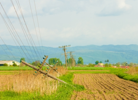 outage: View of fallen telephone poles on the field Stock Photo