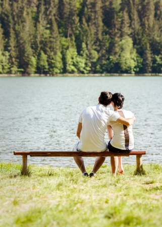 Young lovers sitting on wooden bench photo