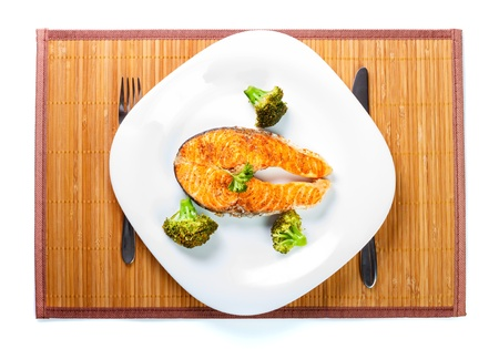 prepared food: Served salmon meat with delicious broccoli on white plate.
