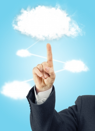 Male hand wearing suit pointing to white cloud in the blue sky. Connection concept. Stock Photo
