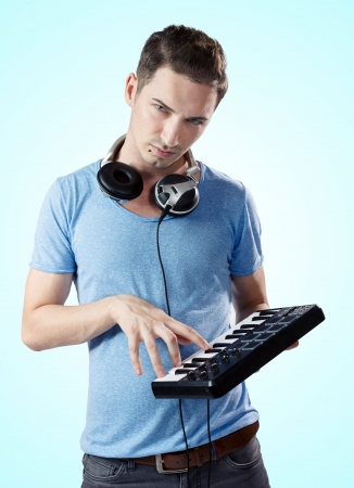 Portrait of young serious deejay with headphones pressing keys on midi controller.Gradient blue background. photo