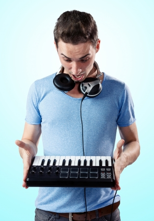 Deejay with headphones holding midi keyboard in hands while being surprised.Gradient blue background. photo