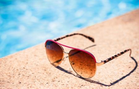 sole occhiali: Brown funky occhiali da sole vicino a nuoto pool.Outdoor scattate con luce naturale.
