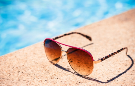 Brown funky sun glasses near swimming pool.Outdoor shot using natural light.
