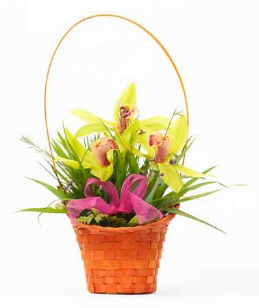 Arrangement of beautiful fresh flowers in wooden basket. Isolated on white background photo