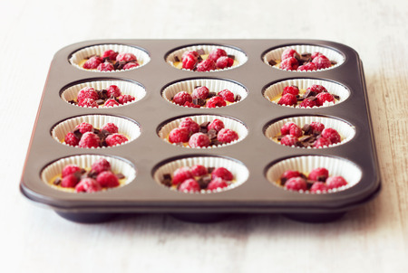 Low angle view of metallic black tray filled with unripe muffins ready to be baked. Muffins are very popular especially in the United States of America. photo
