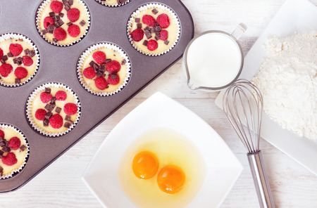 Top view of unripe muffins with ingredients. Two yolks, flour and milk placed on wooden white table. photo