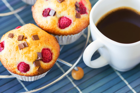 Breakfast with hot coffee and muffins placed on metallic grill. Blue wooden tablecloth underneath photo